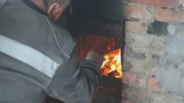 Man kindles fire in the furnace — Stock Video