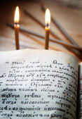 Christian still life with burning candles and open ancient book — Stok fotoğraf