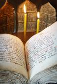 Orthodox Christian still life with open book and burning candles (focus on foreground) — Stock Photo
