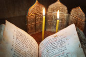 Orthodox religious still life with open ancient book and burning candles (focus on foreground) — Stock Photo