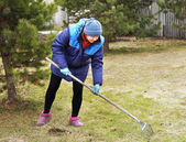 Woman gardener cleans a garden with the rake in spring — Stock Photo