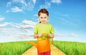 Bambina con un annaffiatoio sta nel campo — Foto Stock