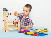 Adorable child playing with wooden building toys — Stock Photo
