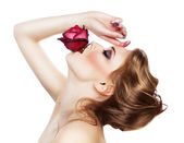 Sensual woman with red rose in mouth — Стоковое фото