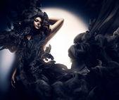 Attractive woman in black smoke — Stock Photo