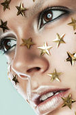 Woman with gold stars on face — Stock Photo