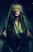 Mysterious woman in green leaves — Stock Photo