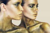 Two pretty women in gold glitters — Stock Photo