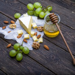 Cheese with grapes, honey and nuts — Stock Photo #65986985