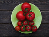 Tomatoes on green plate — Stock Photo