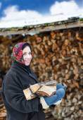 Woman in ethnic costume with firewood — Stock Photo