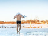 Man wipes towel after swimming in  freezing hole — Stock Photo