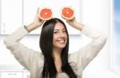 Funny girl holding citrus in the kitchen — Stockfoto