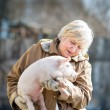 Happy woman holding  newborn piglet — Stock fotografie #67602035