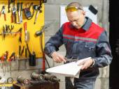 Mechanic worker studying his instructions — Stock Photo