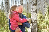 Family in wood collecting birch sap to steel mug — Stock Photo