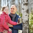 Family to wood collecting birch sap in mug — Stock Photo #70480813