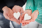 Female and male hands with snow hearts — Stock Photo