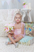 Little girl sitting on small bag with flowers — Foto Stock