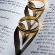 Wedding ring on a book with a shadow in the shape of a heart — Stock Photo #63594453