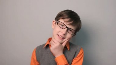Boy teenager smiling experiences happiness holding hand on chin in glasses on gray background decade — Stock Video