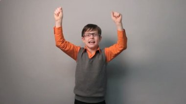 Teenager boy succeeded joy waves his hands for ten years glasses on gray background — Stock Video
