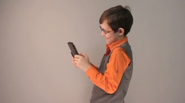 Boy teenager playing tablet keen surprised in glasses on gray background — Stock Video