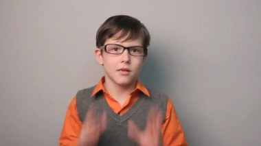 Boy teenager surprise a happiness joy waves his hands for ten years in glasses on gray background — Stock Video