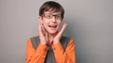 Boy teenager surprise happiness joy waves his hands for ten years in glasses on gray background slow-motion video — Stock Video