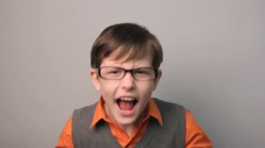 Teenager boy swears row waving his arms opened his mouth in glasses on gray background — Stock Video