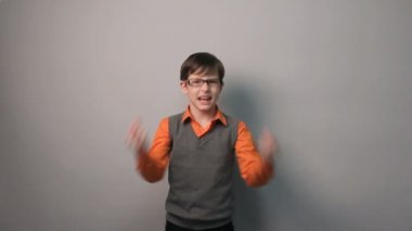 Teenager boy succeeded joy waves his hands for ten years in glasses on gray background — Stock Video