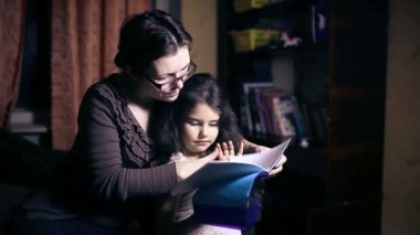 Mom with glasses  woman and  her daughter do homework teen girl reading book decide Leaf — Stock Video