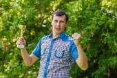 Man holding a sports cup on the street victory against the  gree — Stock Photo