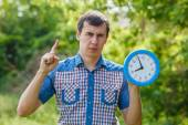 Man holding clock showing thumbs up on a green background  summe — Stock Photo