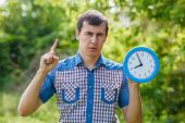 Man holding clock showing thumbs up on a green background summer — Stock Photo