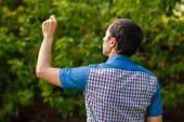 Man tillbaka skriver hand i luften på en grön bakgrund gatan tr — Stockfoto