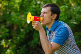 The man in the street holding a plastic speaker shouts on green — Stock Photo
