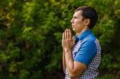 The man in the street to pray to God on a green background leave — Stock Photo