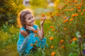 Teen girl sitting on his haunches and touching orange flower in — Stock Photo