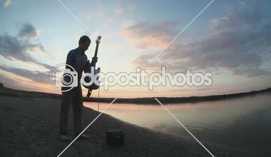 Mužské kytarista muž pouliční muzikant hraje na elektrickou kytaru při západu slunce do vody slunce zapadá — Stock video