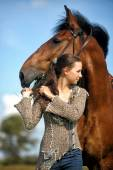 Beautiful young teen girl with the brown horse — Stock Photo