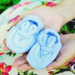 Pregnant woman with a belly holding baby shoes. — Stock Photo #60413199