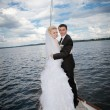 Happy bride and groom hugging on a yacht — Stock Photo #61963061