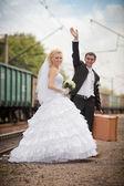 El novio y la novia con una maleta en la estación de tren — Foto de Stock