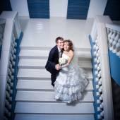 Happy bride and groom on ladde — Stock Photo