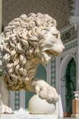 Sculpture of lion with a ball on a background of palace — Stock Photo
