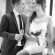 Groom with a glass of champagne and the bride with a bouquet from roses in cafe — Stock Photo #61989387