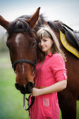 Portrait of the beautiful girl with a brown horse in park — Stock Photo