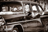 Cheerful groom at a wheel of a black old retro of the car — 图库照片