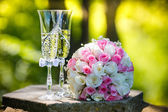 Wedding rings with roses and glasses of champagne — Stock Photo